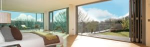 Bifold Door Leading From a Modern Bedroom out to a Garden