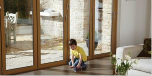 A Child Playing with His Toys Next to a Bifold Door